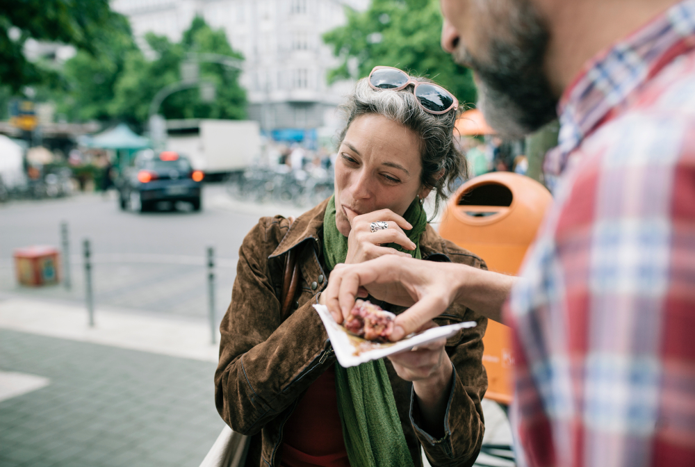 A Woman Enjoying Streetfood With Her Partner