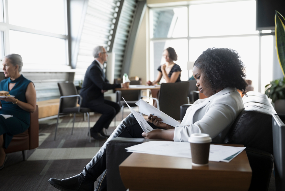 Focused Businesswoman Reviewing Paperwork In Business Lounge